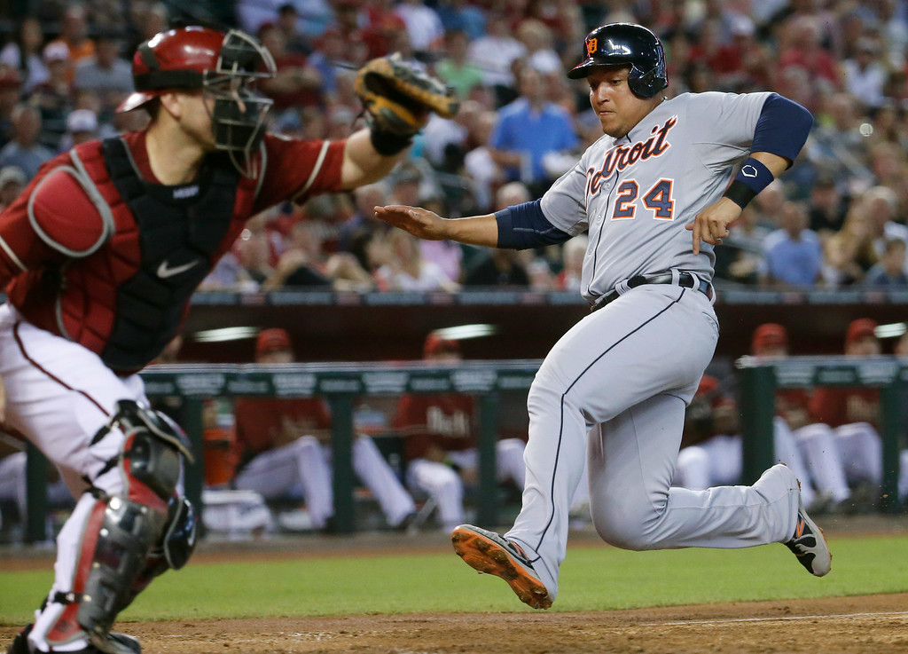 . Detroit Tigers\' Miguel Cabrera (24) scores on a sacrifice fly by teammate Alex Avila as Arizona Diamondbacks catcher Miguel Montero makes the catch during the fourth inning of a baseball game, Wednesday, July 23, 2014, in Phoenix. (AP Photo/Matt York)