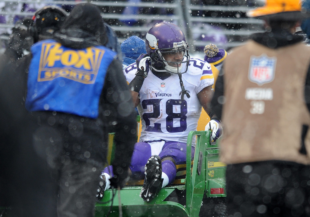 . Minnesota Vikings running back Adrian Peterson is carted off the field after injuring his ankle on a play in the second quarter of an NFL football game against the Baltimore Ravens, Sunday, Dec. 8, 2013, in Baltimore. (AP Photo/Gail Burton)