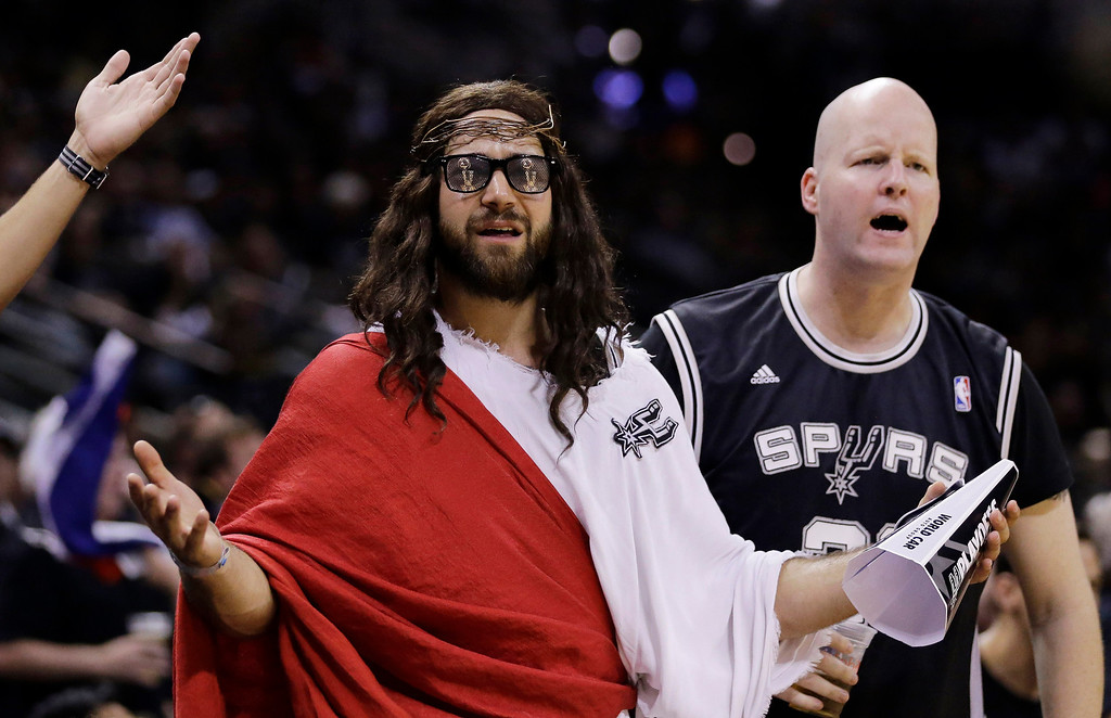 ". Fans, including ""Spurs Jesus\"", center, react to a call during the second half in Game 1 of the NBA basketball finals between the San Antonio Spurs and the Miami Heat on Thursday, June 5, 2014 in San Antonio. (AP Photo/Eric Gay)"