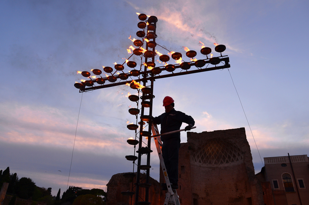 . A worker lights candles on the cross before the Celebration of the Way of the Cross on Good Friday on April 18, 2014 at the Colosseum in Rome.  (ALBERTO PIZZOLI/AFP/Getty Images)