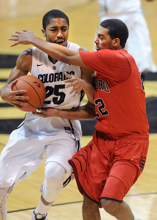 . Spencer Dinwiddie of CU tries to get  past Evan Cooper (22) of Hartford on his way to the basket during the second half of the December 29, 2012 game in Boulder. (Cliff Grassmick / Daily Camera) December 29, 2012