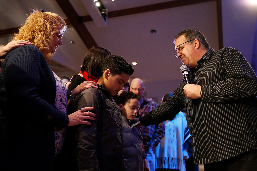 . Pastor Mark Ledford invites the congregation to pray over Adrianna Melo and her two sons during the 9:30 service at the Church of the Nazarene in Westerville, Ohio, on Sunday, Feb. 11, 2018. Melo\'s husband Raul Melo is an Ohio State Highway Patrolman based in Columbus.  (Sam Greene/The Cincinnati Enquirer via AP)