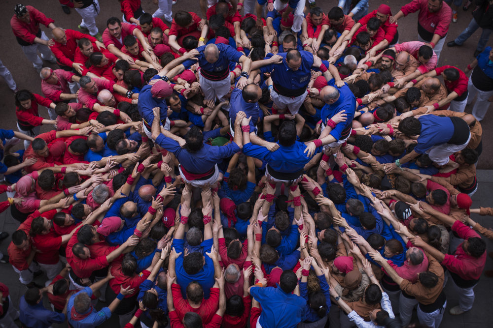 ". Members of the Castellers ""Vila de Gracia\"" start forming their famous human tower called \""castell\"" in the Barcelona neighborhood of Gracia, Catalonia, Spain on Sunday May 19 2013. A \""castell\"" is a human tower traditionally built during festivals in many places in Catalonia. At these festivals, several \""colles\"" or teams compete to build the most impressive towers they can. (AP Photo/Emilio Morenatti)"