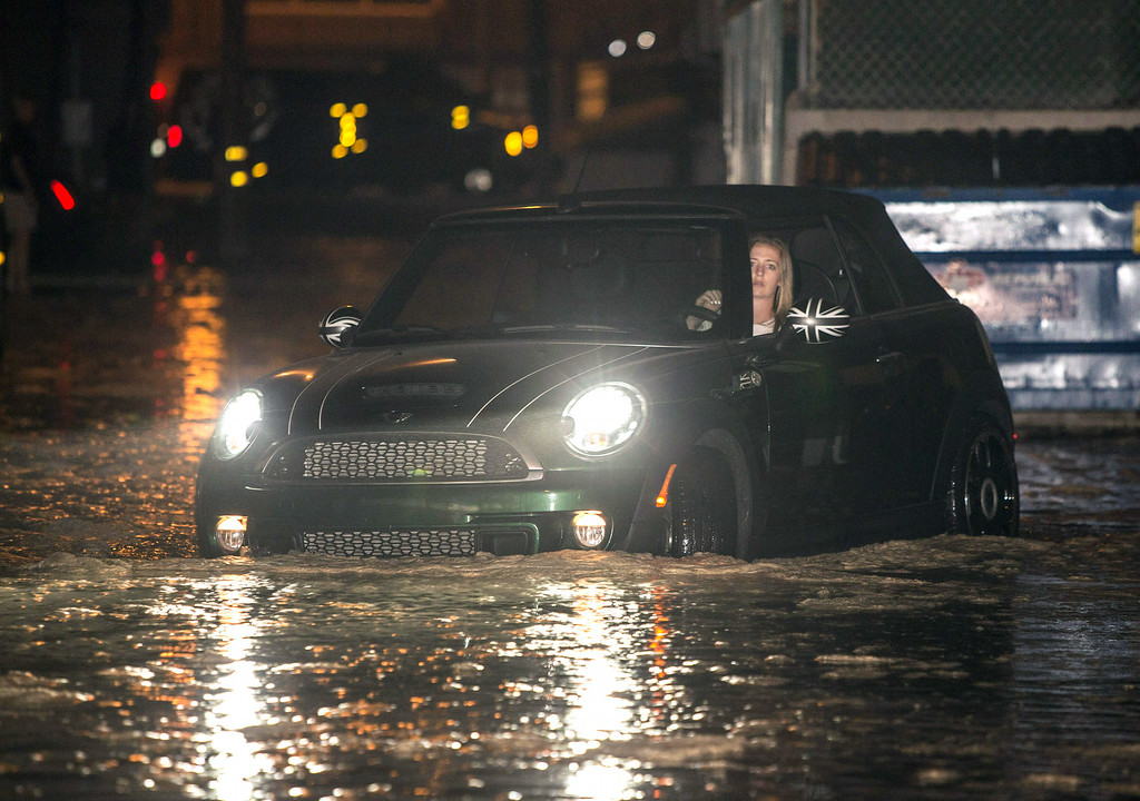 . In this Tuesday, Aug. 26, 2014 photo, a woman drives through a flooded street after high tide and large waves caused heavy flooding in Seal Beach, Calif.  (AP Photo/Kevin Warn)