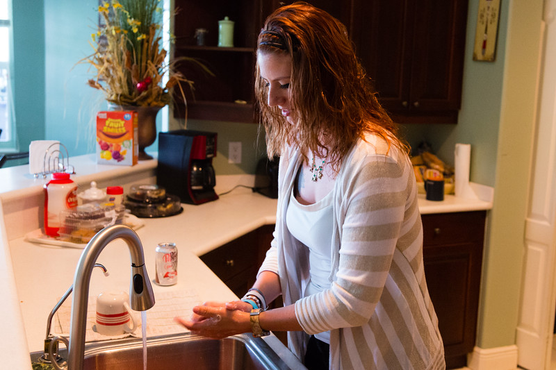 Shelby Sparrow, 21, of Plantation, Florida, washes her hands after handling the pork chops she will be serving for dinner at the All About Recovery younger women's sober home in Loxahatchee, Florida on Wednesday, June 1, 2016. Sparrow, a recovering heroin addict has been in the sober home since February 2016 and has been clean for five months. (Joseph Forzano / The Palm Beach Post)