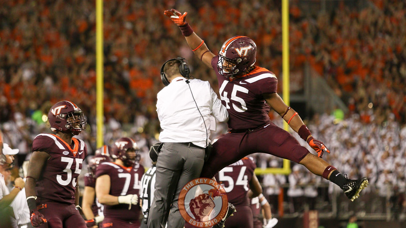 DE TyJuan Garbutt celebrates with an assistant coach after the Hokies recover the ball on downs after a botched Notre Dame punt. (Mark Umansky/TheKeyPlay.com)