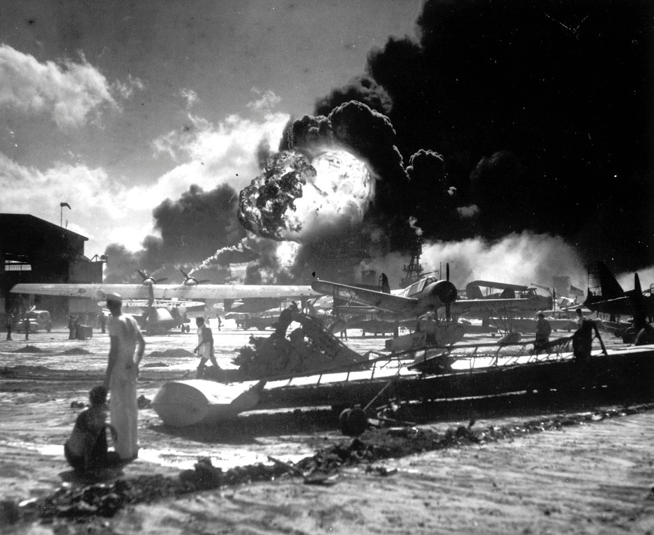 . In this image provided by the U.S. Navy, sailors stand among wrecked airplanes at Ford Island Naval Air Station as they watch the explosion of the USS Shaw in the background, during the Japanese surprise attack on Pearl Harbor, Hawaii, on December 7, 1941. (AP Photo/U.S. Navy)