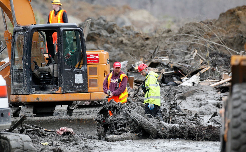 . Workers use heavy equipment in a debris field at the scene of a deadly mudslide, Wednesday, March 26, 2014, in Oso, Wash. Sixteen bodies have been recovered, but authorities believe at least 24 people were killed. And scores of others are still unaccounted for, although many of those names were believed to be duplicates or people who escaped safely. (AP Photo/Rick Wilking, Pool)