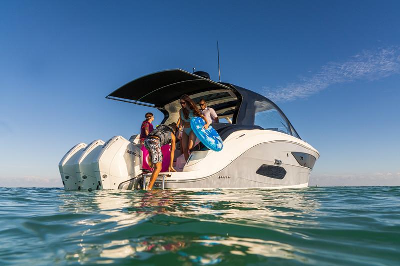 2021-Sundancer-370-Outboard-DAO370-lifestyle-starboard-stern-three-quarter-family-life-jacket-swim-ladder-07435.jpg