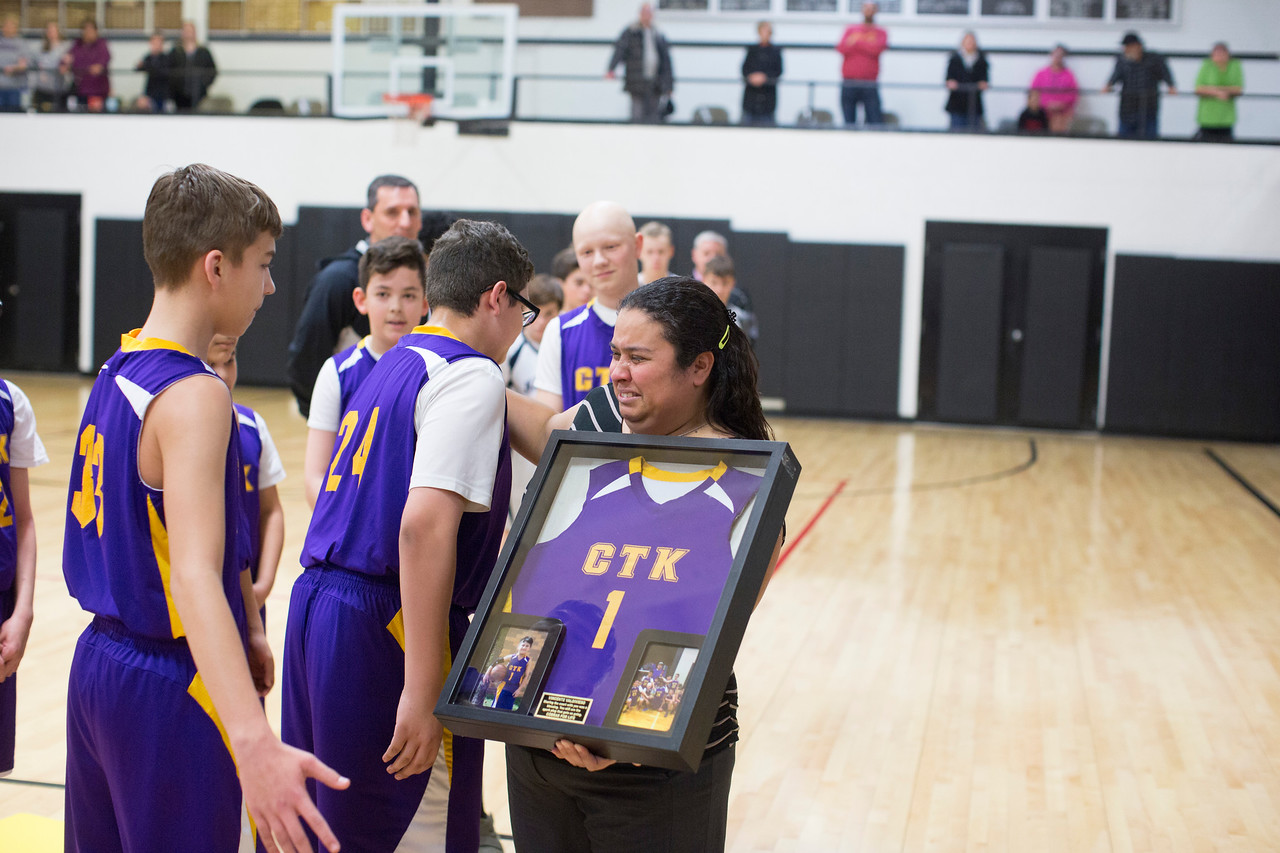 Head coach Luis Pineda, at Christ the King, hugs Angela Rodriguez (Vinny's mom) while her daughter, Selena Valdivieso looks on. Coach is holding a framed jersey of Vinny's. <br /> Coach can be contacted at 913-787-1977 or Chumlee82@gmail.com