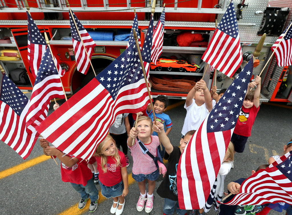 """. Kindergarten students at Virginia Ave. Charlotte DeHart Elementary School in Winchester, Va. wave their American flags after a visit from area first responders that included an appearance by a fire truck during the \""""Salute to Our Heroes\"""" event at the school Thursday, Sept. 11, 2014. (AP Photo, The Winchester Star, Jeff Taylor)"""
