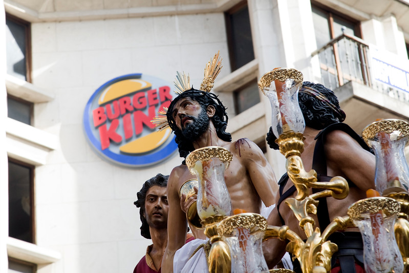 An image of Christ in front of Burger King logo during Holy Week processions, Seville, Spain