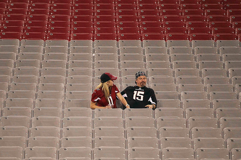 . Dejected Arizona Cardinals fans sit in the stands after their 28-13 loss to the Chicago Bears during their NFL football game in Phoenix, Arizona December 23, 2012. REUTERS/Darryl Webb