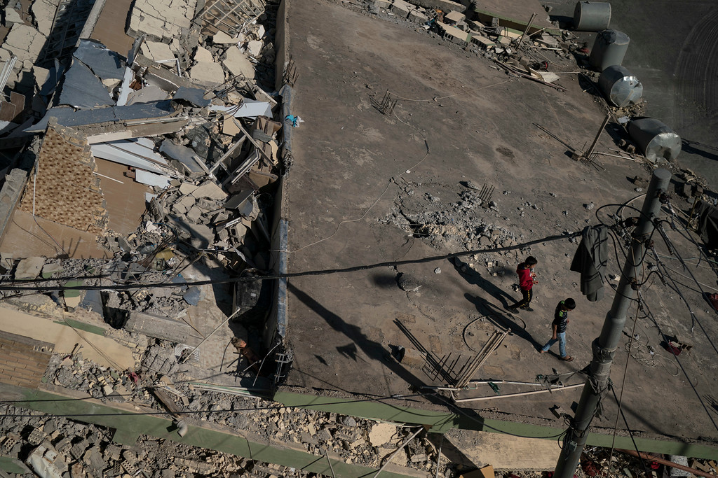 . Boys walk on the roof of a destroyed house after an earthquake in the city of Darbandikhan, northern Iraq, Monday, Nov. 13, 2017. Authorities reported that a powerful 7.3 magnitude earthquake struck the Iraq-Iran border region on Monday and killed more than three hundred people in both countries, sent people fleeing their homes into the night and was felt far west as the Mediterranean coast. (AP Photo/Felipe Dana)