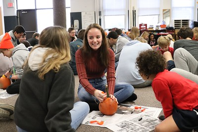 Kindergarteners carve pumpkins with Seniors