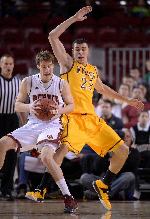 . Denver Pioneers forward Dom Samac (24) puts a move on Wyoming Cowboys forward Larry Nance Jr. (22) during the first half December 15, 2013 Magness Arena. (Photo by John Leyba/The Denver Post)