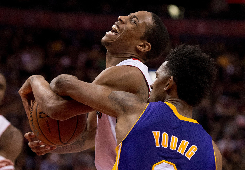 . Toronto Raptors guard DeMar DeRozan, left, is fouled by Los Angeles Lakers guard Nick Young (0) during fourth-quarter NBA basketball game action in Toronto, Sunday, Jan. 19, 2014. (AP Photo/The Canadian Press, Frank Gunn)