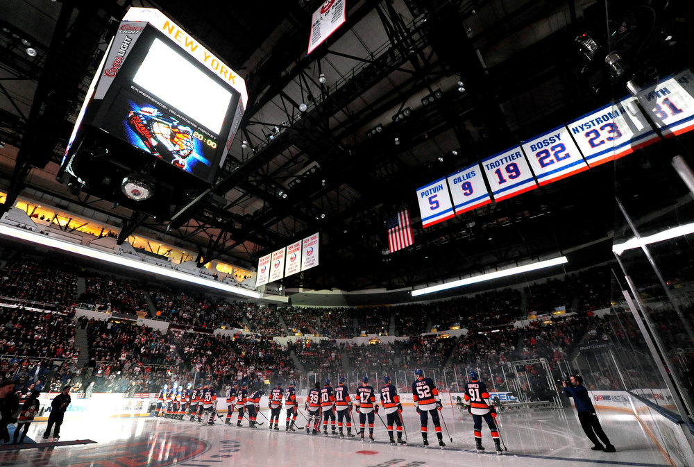 Description of . New York Islanders line up on the ice as they are introduced to the fans during the home opener NHL hockey game against the New Jersey Devils on Saturday Jan., 19, 2013 at Nassau Coliseum  in Uniondale, N.Y. (AP Photo/Kathy Kmonicek)