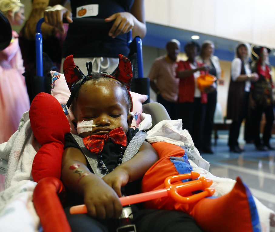 . Tiannah\'Marie King, 11 months, sleeps soundly in her costume during a Halloween celebration in the lobby of All Children\'s Hospital Thursday, Oct. 31, 2013. King, from Riverview, fla., has brain cancer. Her mother, Tiahara Moss, said that she dressed her as a little devil for her first Halloween, because the girl\'s dad, Darryl King, Jr., was also a little devil for his first Halloween. (AP Photo/The Tampa Bay Times, Lara Cerri)