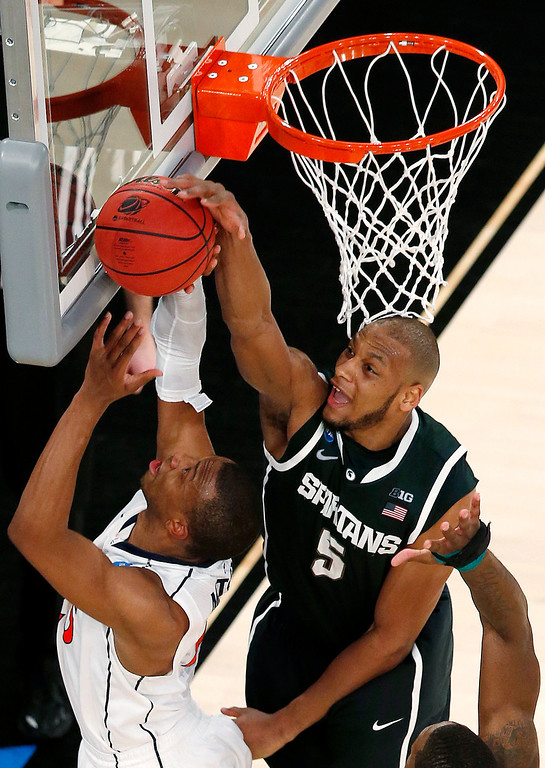 . Michigan State forward Adreian Payne, top, blocks a shot by Virginia forward Akil Mitchell during second half of a regional semifinal at the NCAA men\'s college basketball tournament, early Saturday, March 29, 2014, in New York. (AP Photo/Julio Cortez)