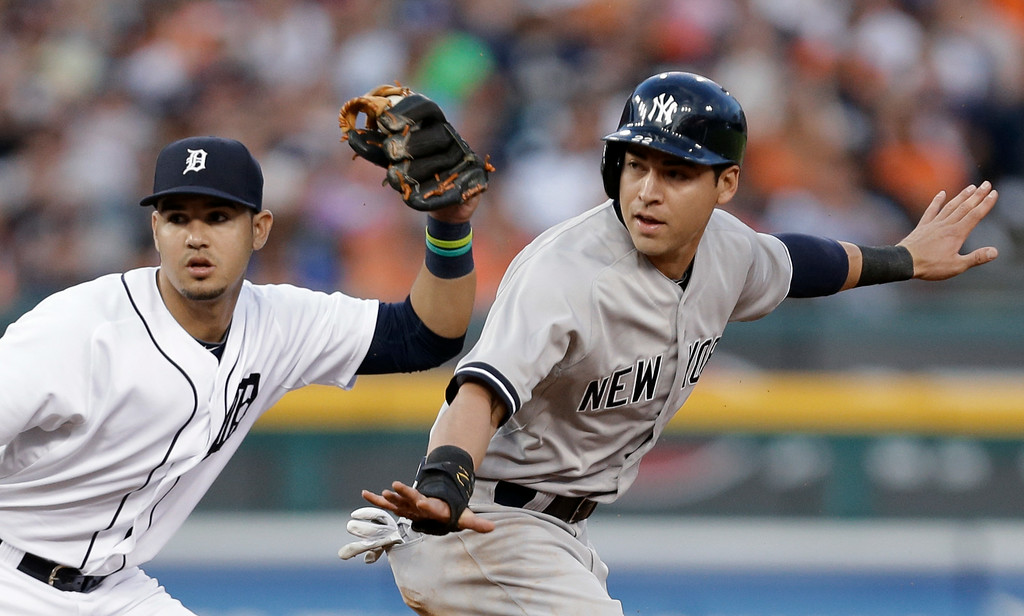 . New York Yankees\' Jacoby Ellsbury, right, signals safe after stealing second base as Detroit Tigers shortstop Eugenio Suarez holds the ball in the third inning of a baseball game in Detroit, Wednesday, Aug. 27, 2014. (AP Photo/Paul Sancya)