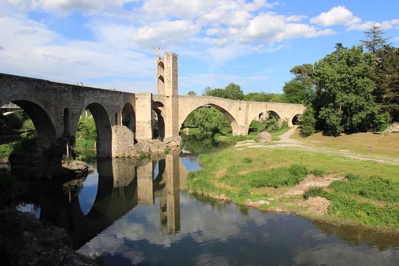 Besalu's 12th century bridge reflects into the river. It's one of many day trips from Girona, Spain.