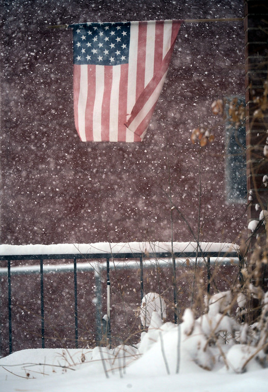 . DENVER, CO. - MARCH 23RD: An American flag whips in the wind during a steady snowstorm on a house near Wesley Ave. and Sherman St. in Denver, Colorado March 23RD, 2013. (Photo By Andy Cross/The Denver Post)