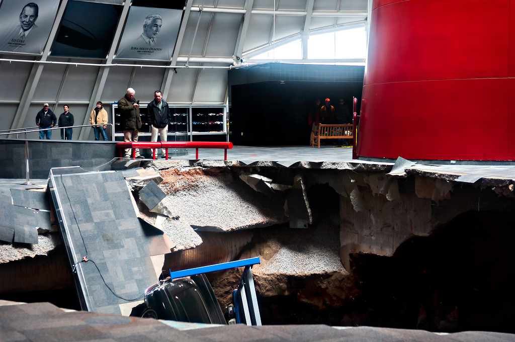 . Officials view a sinkhole that opened up in the Skydome showroom, Wednesday, Feb. 12, 2014, at the National Corvette Museum in Bowling Green, Ky. Eight display cars were swallowed by the hole. (AP Photo/Daily News, Miranda Pederson)