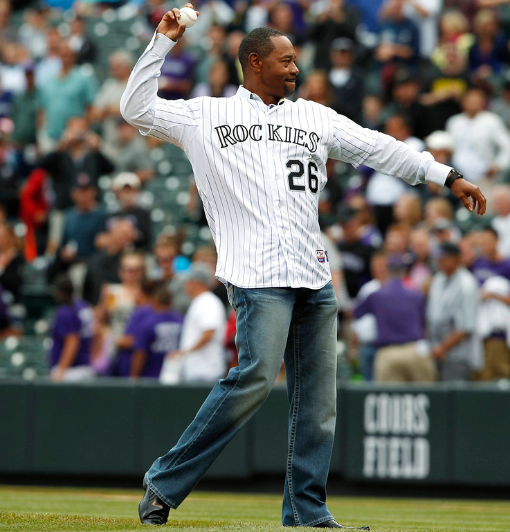 . Retired Colorado Rockies outfielder Ellis Burks tosses out the ceremonial first pitch on his bobble head day as the Rockies host the Milwaukee Brewers in the first inning of a baseball game in Denver on Sunday, July 28, 2013. (AP Photo/David Zalubowski)