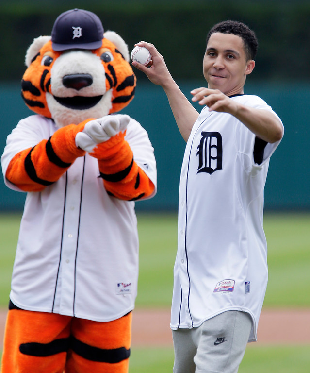 . Michigan State basketball player Travis Trice throws out the ceremonial first pitch under the watch of Paws before the Detroit Tigers baseball game against the Oakland Athletics at Comerica Park, Thursday, June 4, 2015, in Detroit. (AP Photo/Duane Burleson)