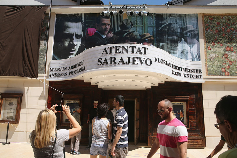 . Visitors walk past a cinema that is showing a film about the assassination of Austrian Archduke Ferdinand by Serbian secessionist Gavrilo Princip in the mock-village of Andricgrad on St. Vitus Day in Srpska Republika on June 28, 2014 in Visegrad, Bosnia and Herzegovina. Serbian leaders are scheduled to hold ceremonies at Andricgrad later in the day to mark the centenary of the 1914 assassination, an event that propelled Europe into World War I. The city of Sarajevo is holding its own commemoration, though Serbian leaders are boycotting the Sarajevo events, claiming the Bosniaks have turned the commemoration too partisan. Andricgrad was built by Serbian film director Emir Kusturica and will become the set for a film about Yugoslav poet Ivo Andric.  (Photo by Sean Gallup/Getty Images)