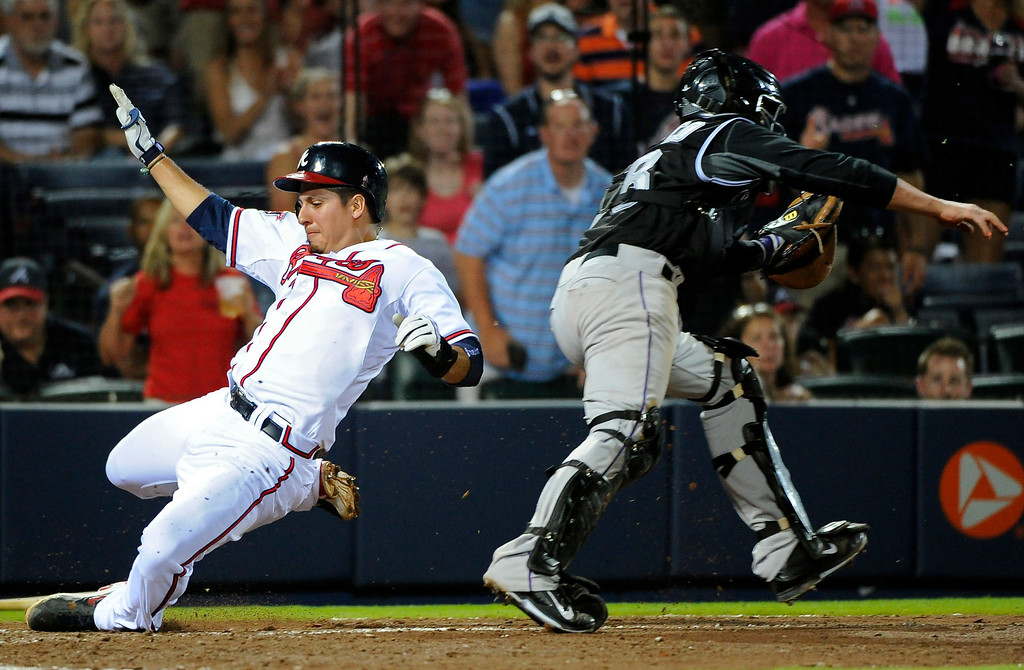 . Atlanta Braves\' Ramiro Pena, left, scores past Colorado Rockies catcher Jordan Pacheco on hit by Gerald Laird to break a 2-2 tie during the eighth inning of a baseball game Friday, May 23, 2014, in Atlanta. (AP Photo/David Tulis)