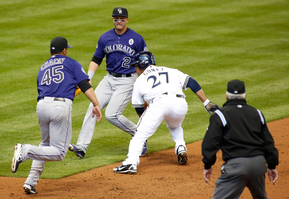 . Milwaukee Brewers center fielder Carlos Gomez (27) is caught in a run down by Colorado Rockies pitcher Jhoulys Chacin (L) as shortstop Troy Tulowitzki looks on during the second inning in a MLB National League baseball game in Milwaukee, Wisconsin April 1, 2013. REUTERS/Darren Hauck