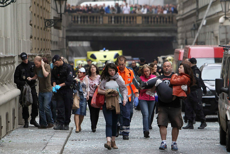 . Injured people leave an area after an explosion in Prague April 29, 2013. The explosion in central Prague on Monday injured about a dozen people and others were trapped in a building damaged by the blast, a Reuters witness and emergency services officials said.  REUTERS/David W Cerny