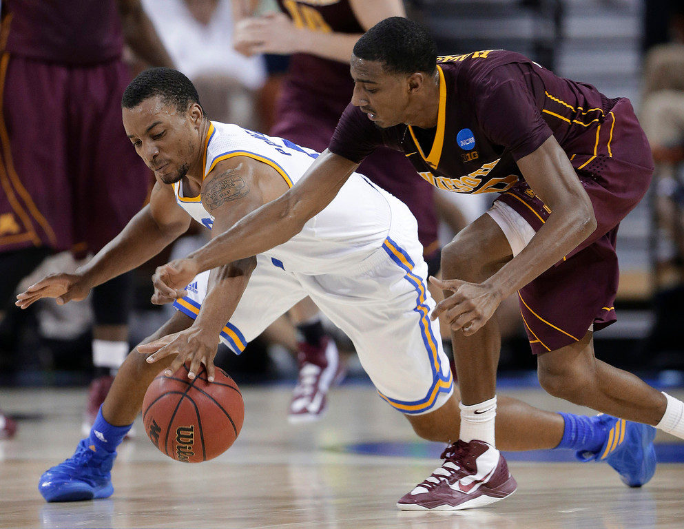 . UCLA\'s Norman Powell, left, and Minnesota\'s Austin Hollins, right, reach for the ball during the first half of a second-round game of the NCAA men\'s college basketball tournament Friday, March 22, 2013, in Austin, Texas. (AP Photo/Eric Gay)