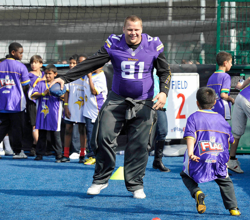 . Minnesota Vikings Chase Baker works with a young football player. (NFL: Sean Ryan)