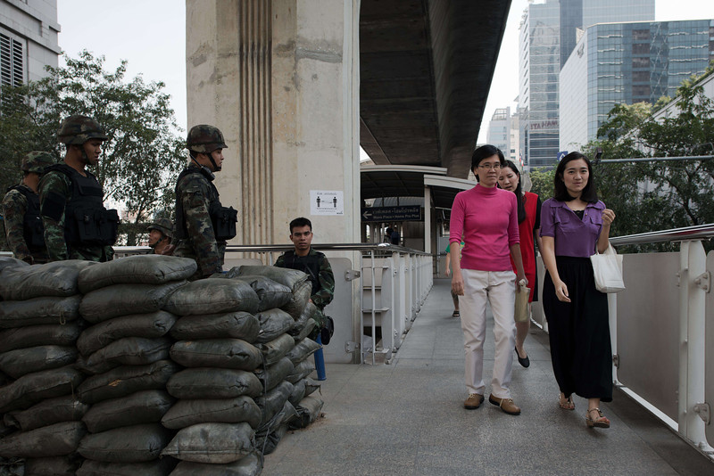 . Thai army soldiers stand behind sand bags as people walk by on an over pass bridge in Bangkok on January 16, 2014. Thailand\'s government pleaded with police to arrest opposition protest leaders who have threatened to take the prime minister captive and paralyzed parts of central Bangkok. (NICOLAS ASFOURI/AFP/Getty Images)