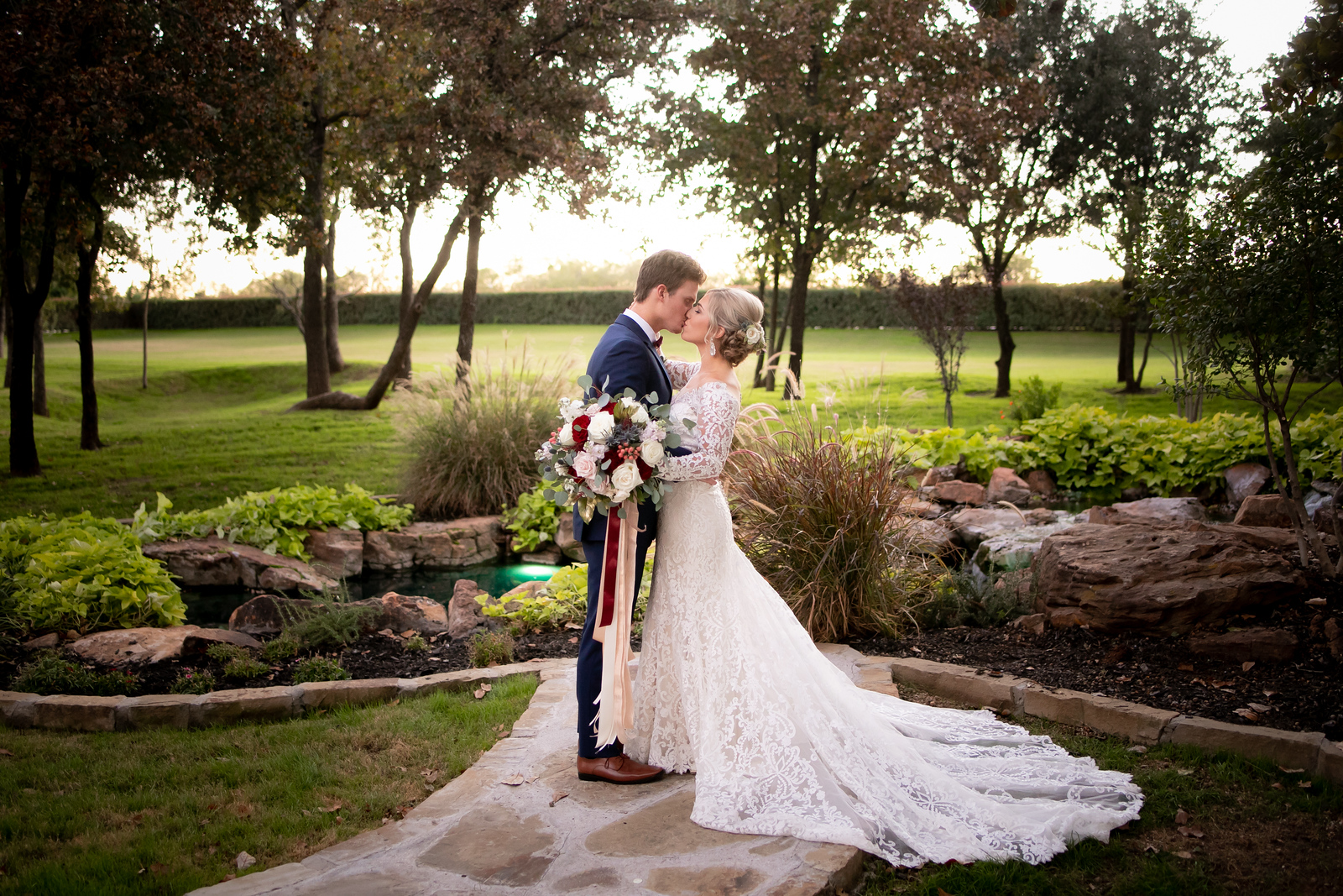 bride and groom share a kiss in a garden at sunset after their wedding ceremony