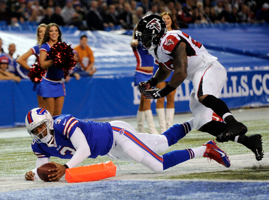 . Buffalo Bills quarterback EJ Manuel (3) scores a touchdown in front of Atlanta Falcons strong safety William Moore during the first half of an NFL football game on Sunday, Dec. 1, 2013, in Toronto. (AP Photo/Gary Wiepert)