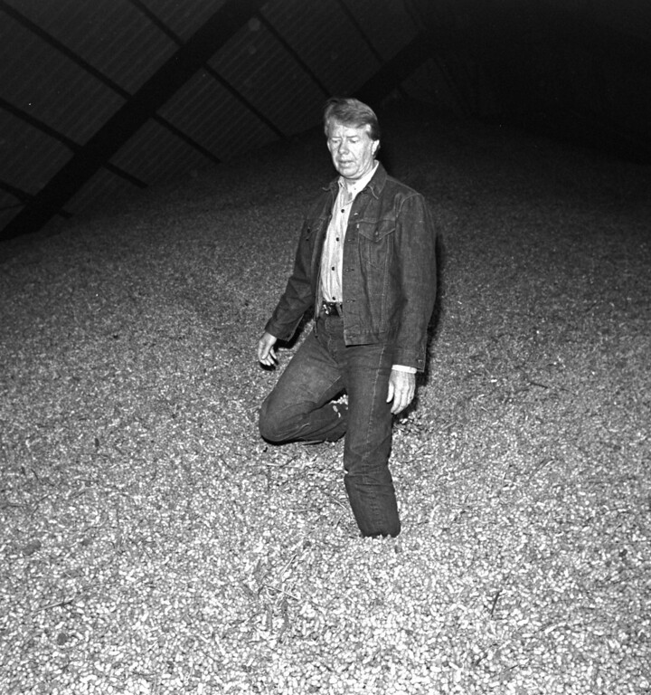 . Jimmy Carter stands in a large mound of peanuts at the Carter Peanut Warehouse in Plains, Ga., September 22, 1976.    The Democratic party presidential nominee took an early morning walk through the warehouse to inspect some of the harvest.  (AP Photo)