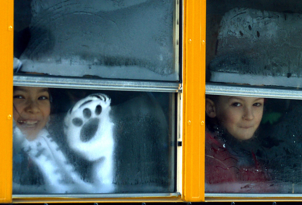 Description of . Sandy Hook Elementary students leave on a school bus  in Newtown, Connecticut on January 3, 2013.  Students at the elementary school where a gunman massacred 26 children and teachers last month were returning Thursday to classes at an alternative campus described by police as