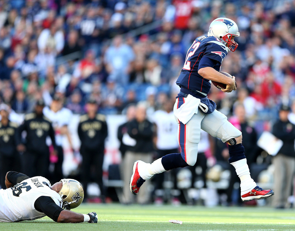 . Tom Brady #12 of the New England Patriots carries the ball as Tom Johnson #96 of the New Orleans Saints defends at Gillette Stadium on October 13, 2013 in Foxboro, Massachusetts.  (Photo by Elsa/Getty Images)