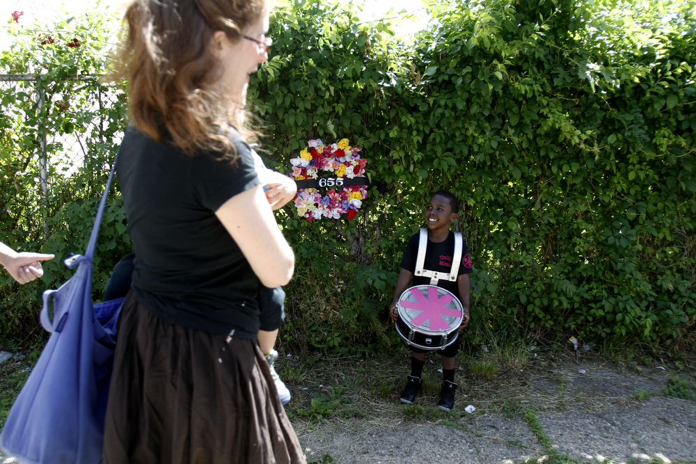 """Description of . Cyion Deas, 5, right, watches with his drum as people arrive at the site of an abandoned home in the impoverished Mantua section Philadelphia on Saturday, May 31, 2014. The cultural and memorial project called """"Funeral for a Home"""" celebrated the dilapidated row house's colorful life before it was knocked down. Organizers from Temple University said it was an effort to commemorate neighborhood history in a city where about 600 houses are torn down each year and 25,000 others sit vacant.(AP Photo/Jessica Kourkounis)"""
