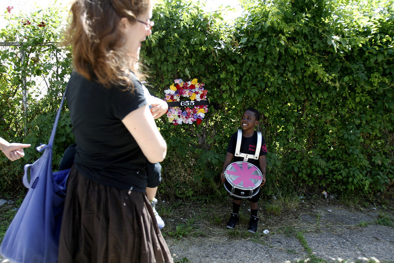 . Cyion Deas, 5, right, watches with his drum as people arrive at the site of an abandoned home in the impoverished Mantua section Philadelphia on Saturday, May 31, 2014. The cultural and memorial project called �Funeral for a Home� celebrated the dilapidated row house\'s colorful life before it was knocked down. Organizers from Temple University said it was an effort to commemorate neighborhood history in a city where about 600 houses are torn down each year and 25,000 others sit vacant.(AP Photo/Jessica Kourkounis)
