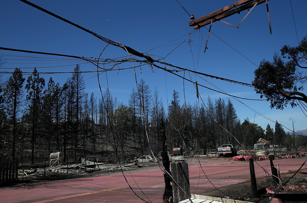 . Downed power lines hang over the remains of destroyed homes on September 16, 2014 in Weed, California. A fast moving wildfire fueled by high winds ripped through the town of Weed on the afternoon of September 15, burning 100 structures including the high school and lumber mill.  (Photo by Justin Sullivan/Getty Images)