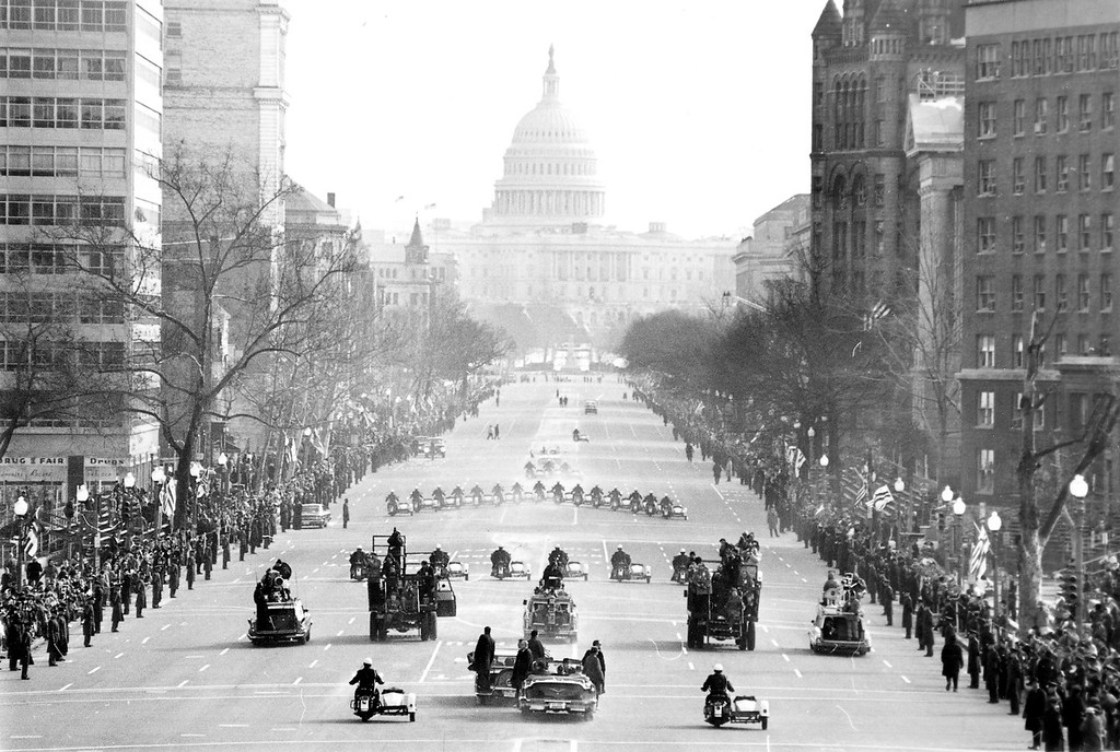 . The motorcade bringing President Johnson to the Capitol for his inauguration moves along Pennsylvania Avenue, January 20, 1965.  Police on motorcycles lead the way. Johnson is in a closed car at lower center with Secret Service agents on the bumper. Another car full of Secret Service men is close by. (AP Photo)