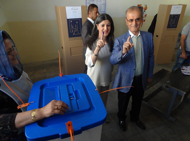 Description of . Governor of Kirkuk Najm al-Din Omar Karim (R) and his wife show their ink-stained fingers after casting their votes in Iraq's first parliamentary election since US troops withdrew at the Khabat polling station north of the Iraqi city of Kirkuk on April 30, 2014. Iraqis streamed to voting centres nationwide, amid the worst bloodshed in years, as Prime Minister Nuri al-Maliki seeks reelection. (MARWAN IBRAHIM/AFP/Getty Images)