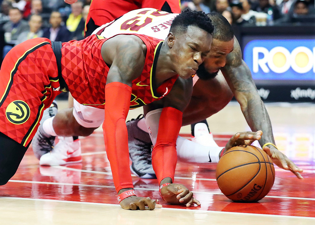 . Atlanta Hawks guard Dennis Schroder grimaces as he collides with Cleveland Cavaliers forward LeBron James while they battle for a loose ball during the second half of an NBA basketball game, Thursday, Nov. 30, 2017, in Atlanta. The Cavaliers won 121-114.  (Curtis Compton/Atlanta Journal-Constitution via AP)