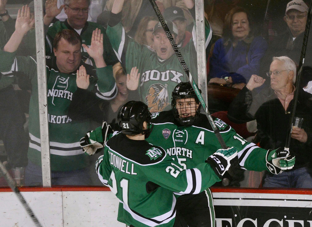 . DENVER, CO. - JANUARY 24:  North Dakota wing Michael Parks (15) celebrates his first period goal with line mate Brendan O\'Donnell (21) . The University of Denver hockey team hosted North Dakota at Magness Arena Friday night, January 24, 2014. Photo By Karl Gehring/The Denver Post