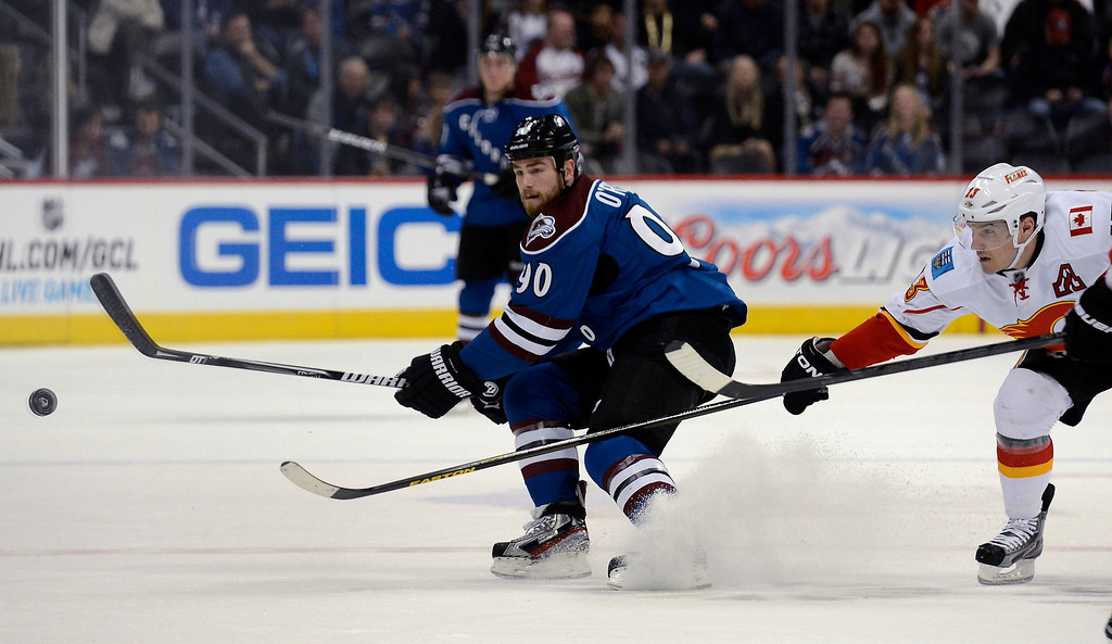 . Ryan O\'Reilly (90) of the Colorado Avalanche dumps the puck in to the Calgary zone as Mike Cammalleri (13) of the Calgary Flames defends on the play in the first period April 8, 2013 at Pepsi Center. (Photo By John Leyba/The Denver Post)